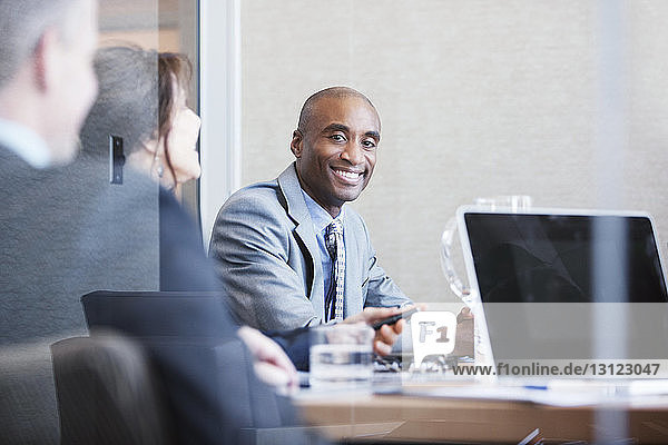 Portrait of smiling businessman in meeting at conference room