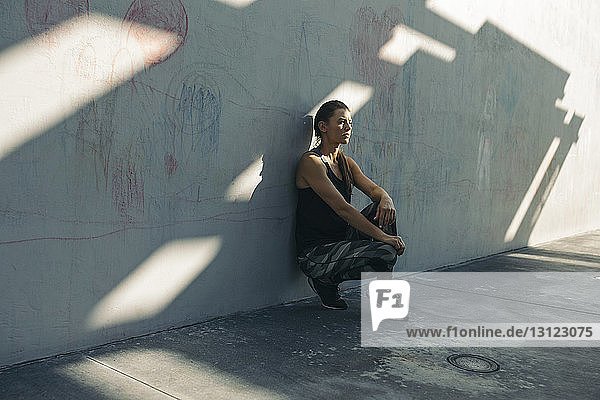 Thoughtful female athlete leaning on wall while crouching at sidewalk
