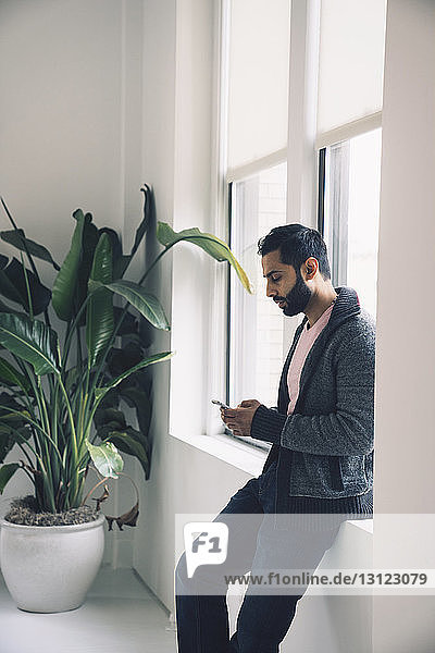 Businessman using smart phone while leaning on window sill in office