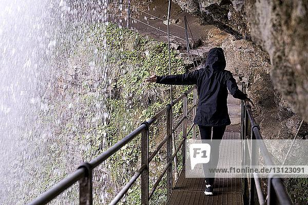 Rear view of woman touching Trummelbach Falls while walking on footbridge under rock