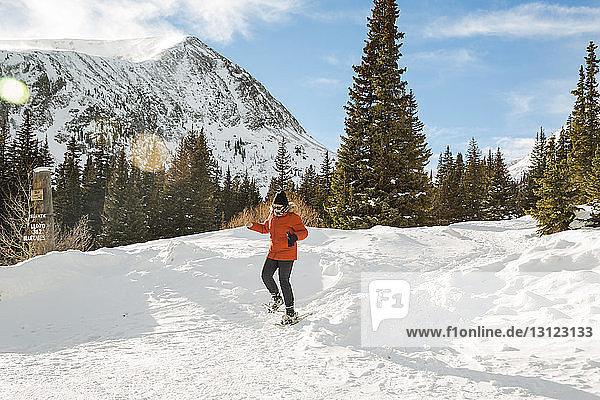 Frau mit Schneeschuhen geht auf schneebedecktem Feld gegen den Himmel
