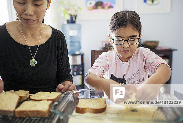Mother and daughter preparing bread at home
