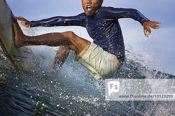 Aufgeregter junger Mann surft auf dem Meer Aufgeregter junger Mann surft auf dem Meer