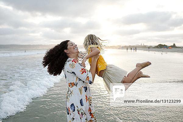 Verspielte Mutter spinnt Tochter am Strand