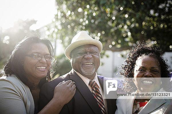 Porträt von glücklichen Eltern mit Tochter im Park stehend
