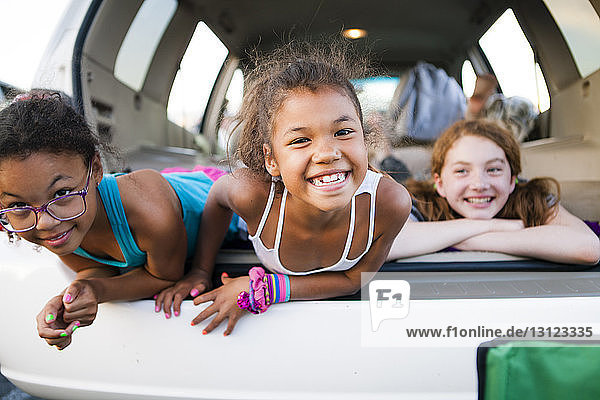 Portrait of carefree sisters lying in car trunk with friend