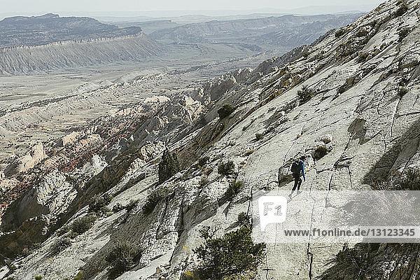 Hochwinkelansicht eines Wanderers  der auf einem Berg gegen den Himmel geht