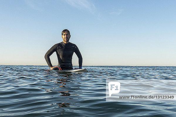 Male surfer sitting on surfboard in sea against clear sky
