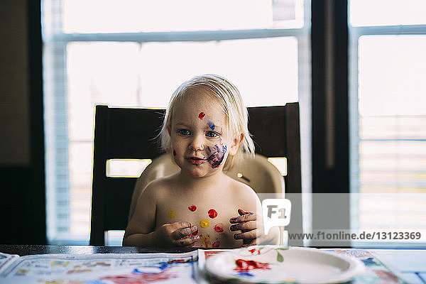 Boy with paint on face looking away while sitting at table