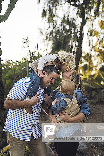 Happy parents with sons standing against plants at park