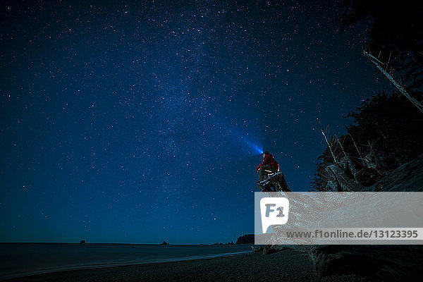 Hiker wearing headlamp sitting on tree trunk at La Push beach against sky at night