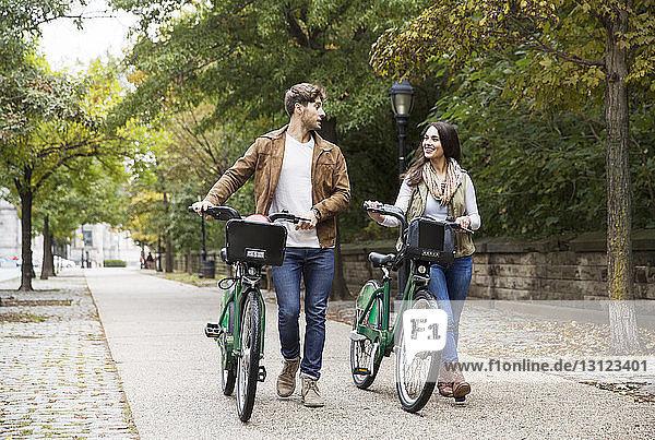 Paar redet beim Gehen mit dem Fahrrad auf der Straße im Park
