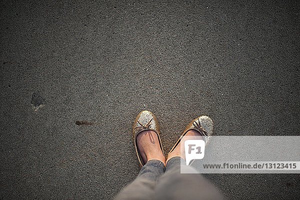 Low section of girl standing on footpath during sunset