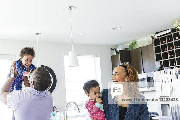 Glückliche Frau sieht Mann an  der ein Mädchen hochhebt  während er zu Hause eine Tochter austrägt