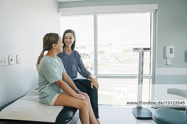 Mutter und Tochter sitzen auf dem Untersuchungstisch im Krankenhaus