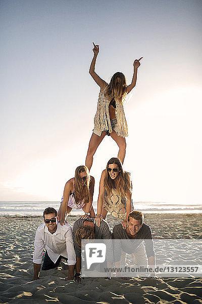 Fröhliche Freunde beim Pyramidenbau am Strand vor klarem Himmel
