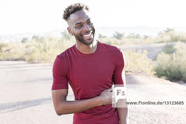 Männlicher Wanderer lächelt  während er an einem sonnigen Tag auf der Straße steht
