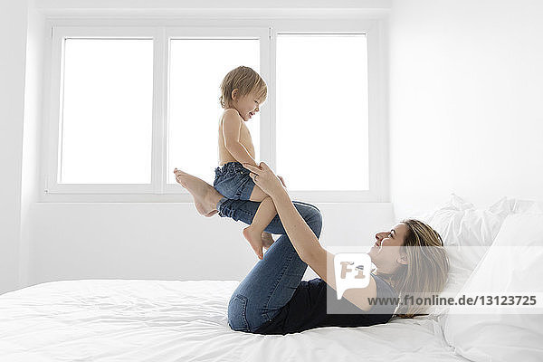 Happy mother playing with shirtless daughter while lying on bed at home