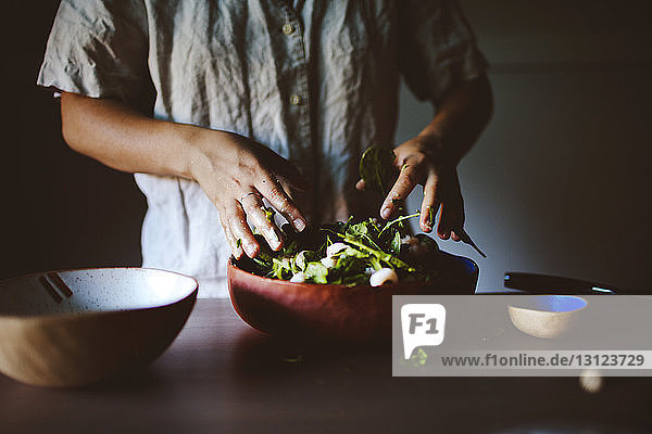 Midsection of woman mixing salad at home
