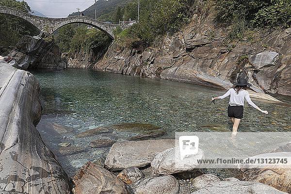 Rückansicht einer Frau  die im Fluss an Felsen entlang geht