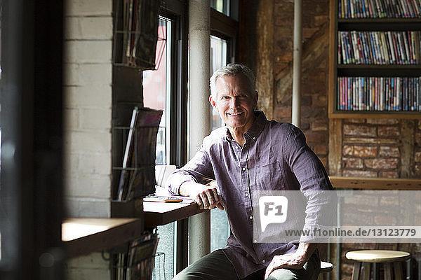 Lächelnder reifer Mann sitzt am Tisch am Fenster im Cafe