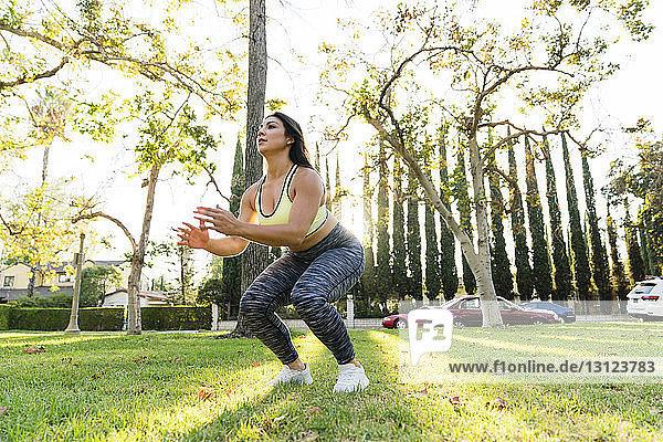 Frau übt Sprungbeugen im Park
