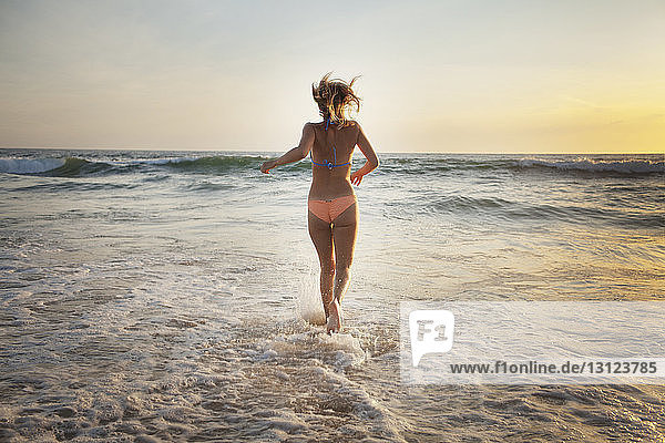 Rear view of woman running on beach during sunset