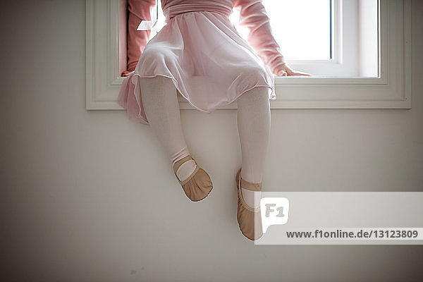 Low section of girl in ballet costume sitting on window sill at home
