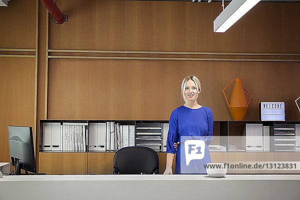 Porträt einer lächelnden Geschäftsfrau,  die im Büro am Schreibtisch steht