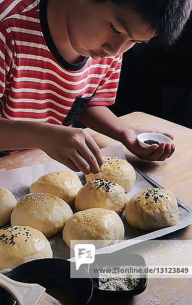 High angle view of boy putting sesame seeds on buns in kitchen at home