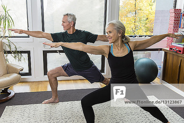 Couple with arms outstretched and legs apart exercising at home