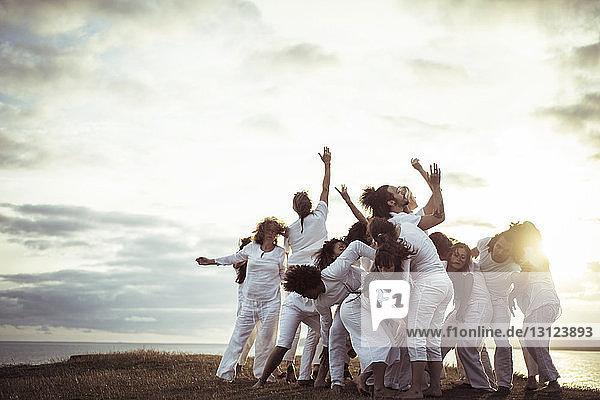 Menschen  die Entspannungsübungen auf dem Feld gegen den Himmel praktizieren