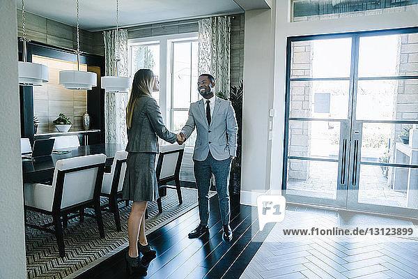 Geschäftsleute in voller Länge beim Händeschütteln  während sie im Sitzungssaal im Büro stehen