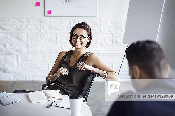 Lächelnde Geschäftsfrau sitzt auf Stuhl im Kreativbüro