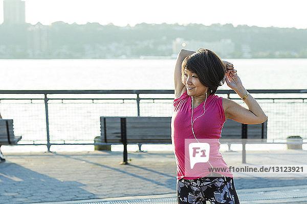 Frau streckt die Arme aus  während sie auf einer Brücke in der Stadt Musik hört