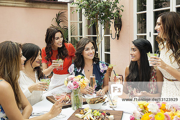Cheerful female friends enjoying lunch at outdoor restaurant