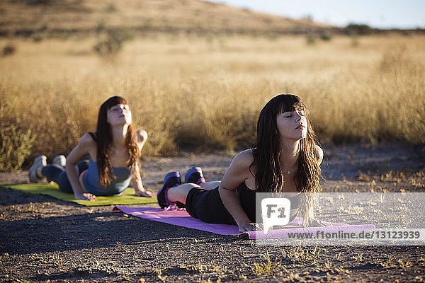 Young women practicing yoga on exercise mat in field