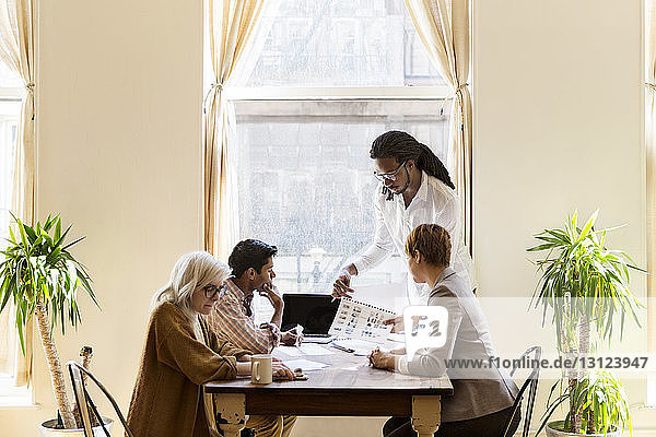 Businessman showing chart to colleagues during presentation in creative office