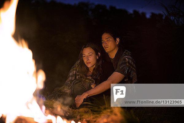 In eine Decke gehülltes Ehepaar sitzt nachts am Lagerfeuer