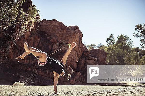 Mann tanzt bei Sonnenschein auf Sand gegen Felsformationen in der Wüste
