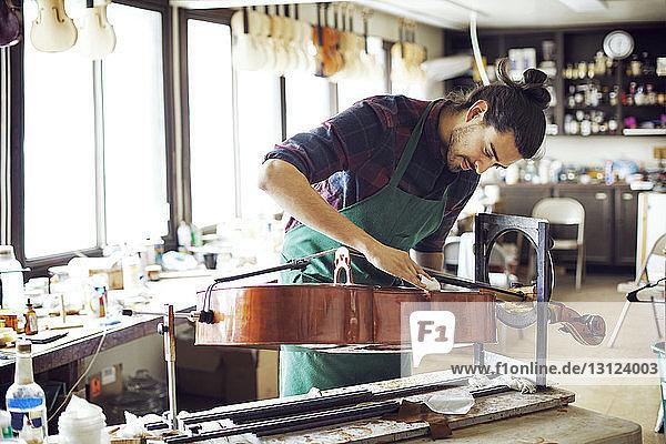 Mann reinigt Geige am Ständer während der Arbeit in der Werkstatt