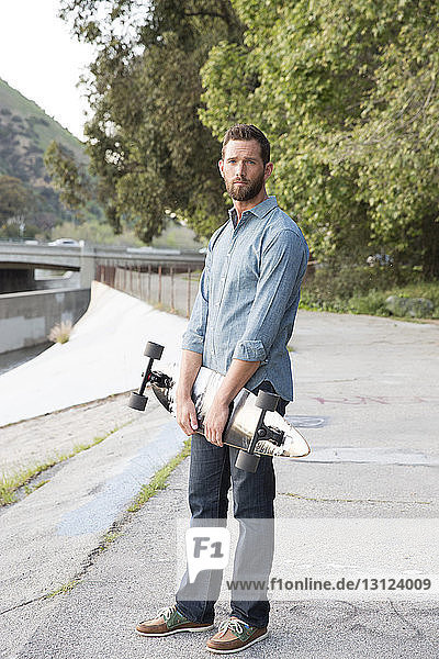 Portrait of man holding skateboard while standing against trees