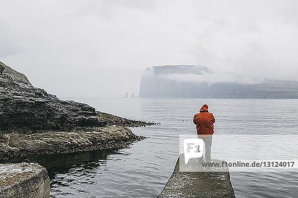 Rear view of hiker in hooded jacket standing on pier against sea during foggy weather