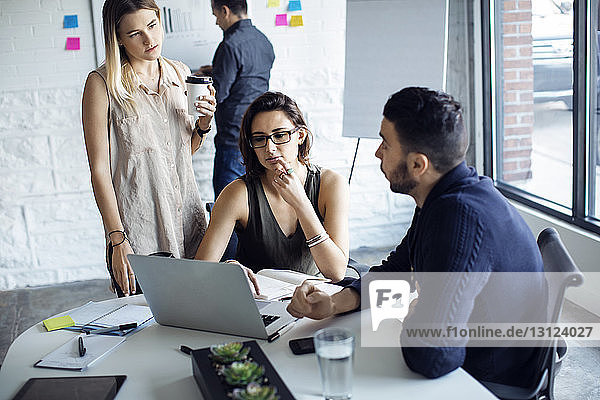 Geschäftsleute mit Laptop bei Diskussionen im Kreativbüro