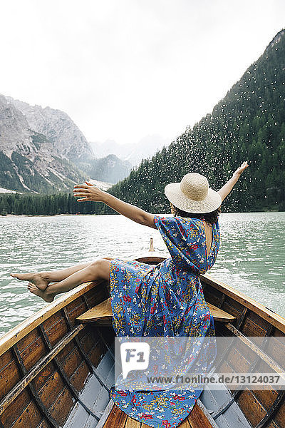 Happy woman enjoying rowboat riding over lake against mountains