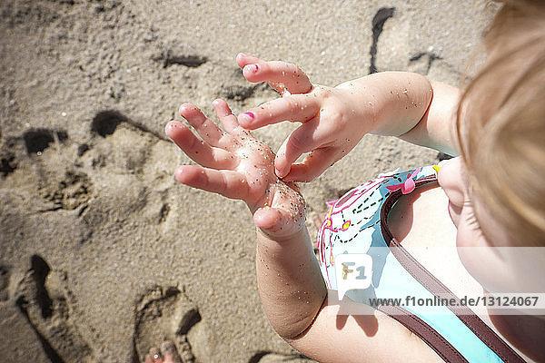 Hochwinkelaufnahme eines Mädchens  das im Sommer am Strand Sand aus ihrer nassen Hand entfernt Hochwinkelaufnahme eines Mädchens, das im Sommer am Strand Sand aus ihrer nassen Hand entfernt
