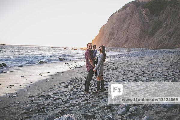 Porträt einer glücklichen Familie  die am Strand vor klarem Himmel steht