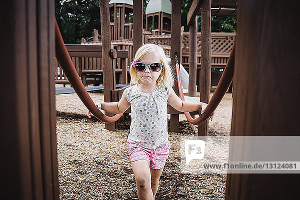 Portrait of girl wearing sunglasses while standing at playground