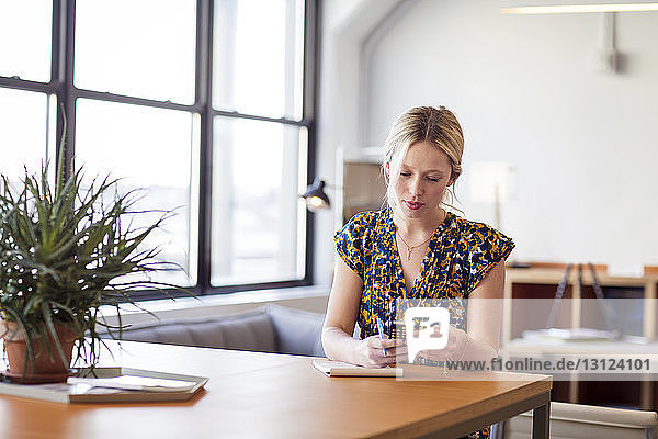 Geschäftsfrau benutzt Smartphone,  während sie im Büro am Tisch sitzt