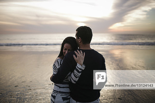 Couple embracing while standing at beach against cloudy sky during sunset